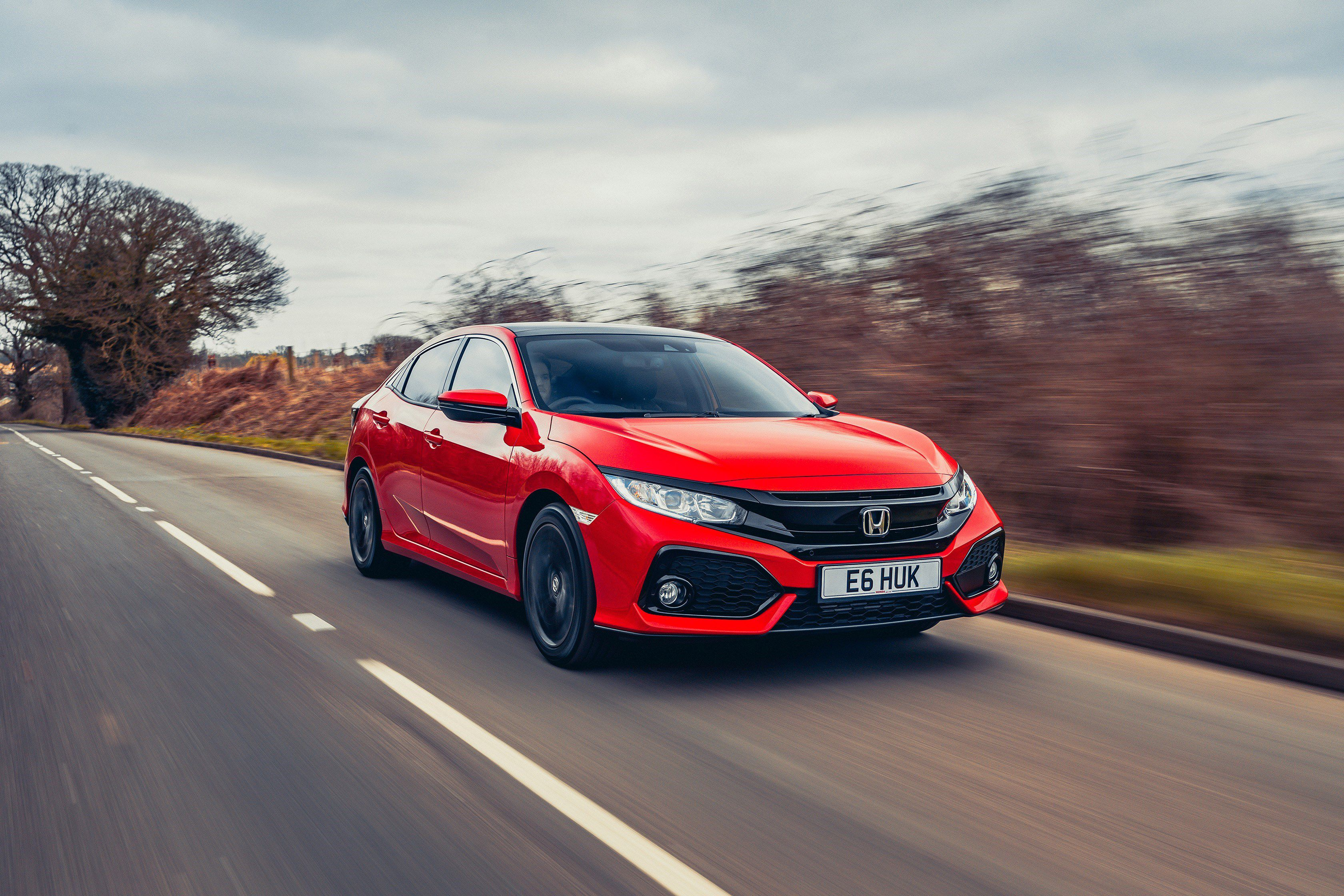 Red Honda Civic diesle driving toward you down a country lane