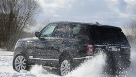 Black range rover driving in the snow