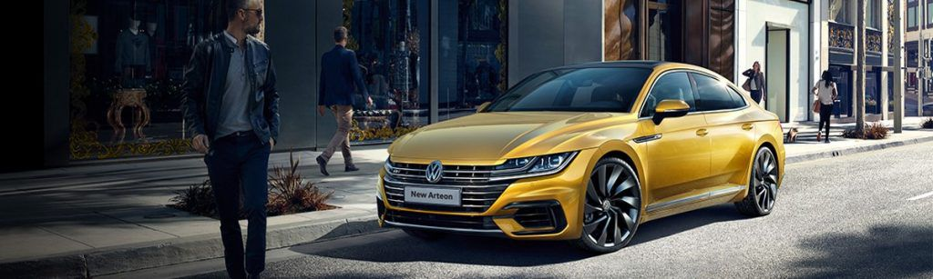 Volkswagen Arteon finished in Turmeric yellow parlked in front of shops