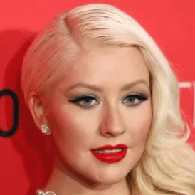 Christina Aguilera with red lipstick smiling at an awards red carpet