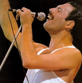 Freddie Mercury from Queen singing into a micrphone with his eyes closed and one arm raised