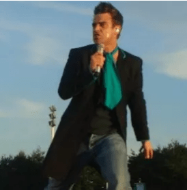 Robbie Williams singing into a microphone with a blackk coat, jeans, black t-shirt and big blue tie