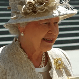 Queen Elizabeth II wearing pearl earrings, pearl necklace and cream coloured hat and blazer with a gold broach