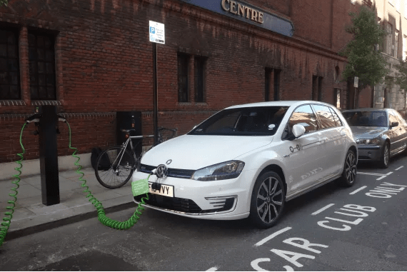 White Volkswagen electric car being charged