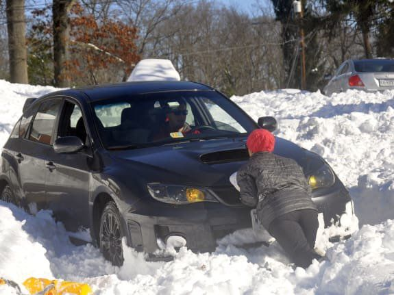 People pushing car trapped in the deep snow