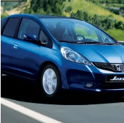 Blue Honda Jazz on the road coming towards you
