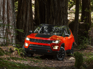 Jeep Compass with headlights on in the woods