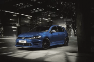 Blue Volkswagen Golf parked in a dark warehouse