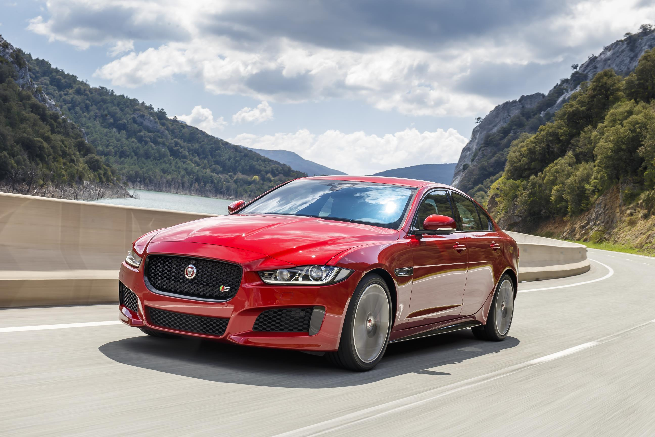 Red Jaguar XE driving towards you on beautiful country road