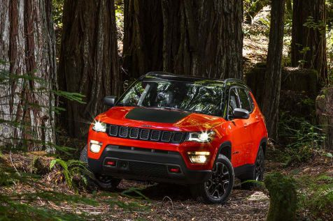 Jeep Compass with lights on parked in forest with trees around