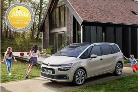 Citroen C4 Grand Picasso parked ona driveway with children playing around it with awards logo in top left corner