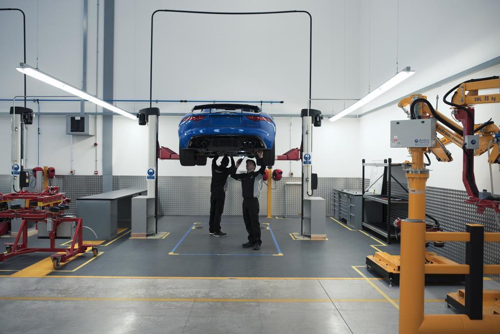 Blue Jaguar car on ramp in workshop being serviced by 2 technicians