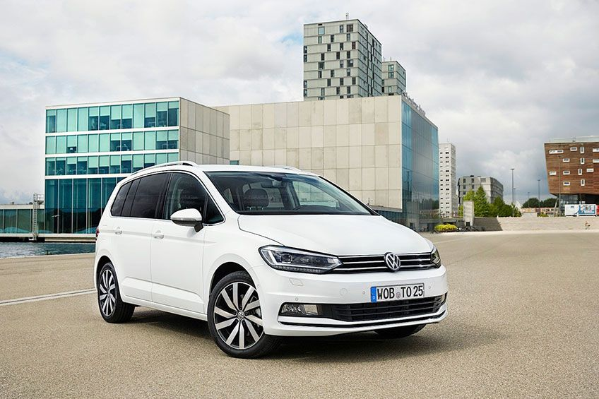 white Volkswagen Touran in fron to very modern building