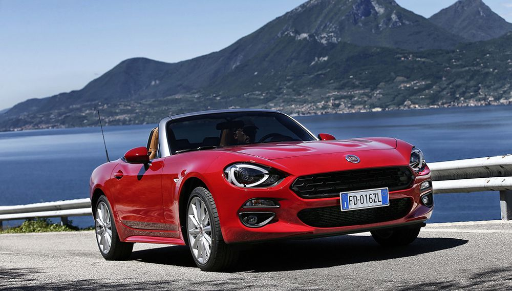 Red Fiat 124 Spider convertible car with roof down parked by the sea in front of mountains
