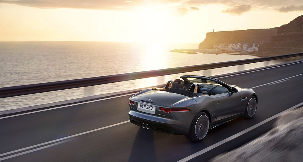 Grey Jaguar F-Type convertible car with roof down by the sea