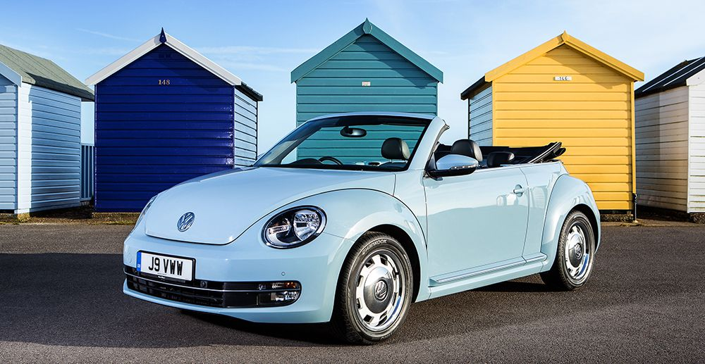 Baby blue Volkswagen Beetle convertible car with roof down parked in front of beach huts