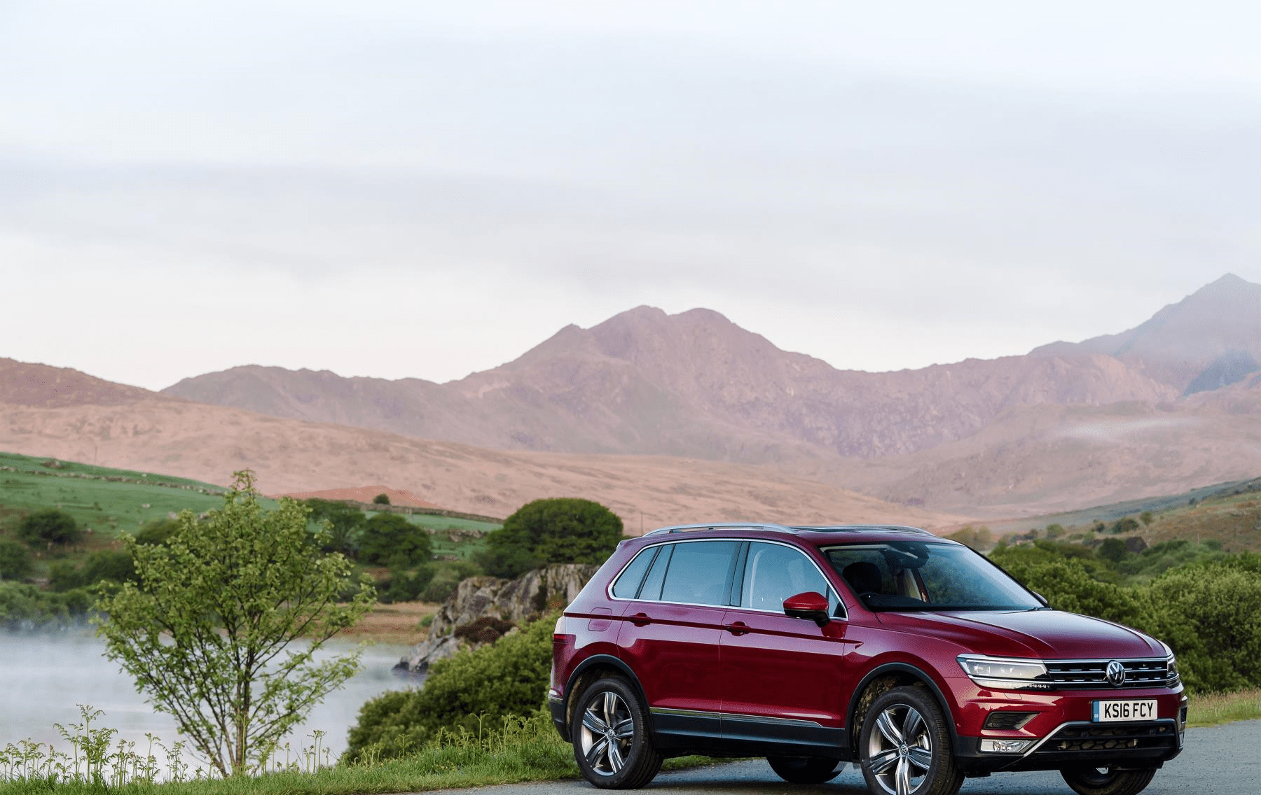 Red Volkswagen Tiguan infront of mountains