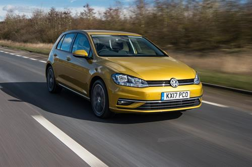 Yellow Volkswagen Polo with 5 doors driving down a road