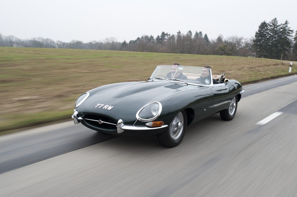A vintage dark green Jaguar E-Type drives along a country road with its soft top down