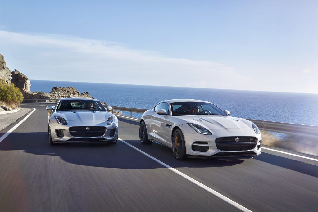 Silver Jaguar F-Type convertible pulling up next to a white Jaguar F-Type coupe as they race along a seafront road