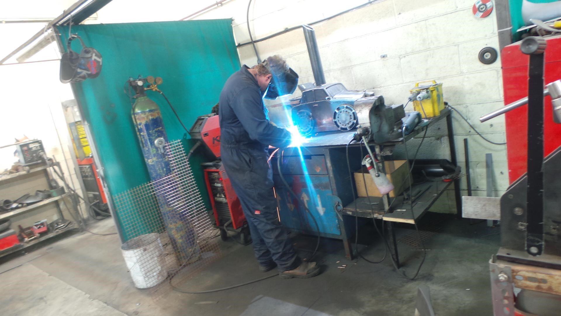 mechanic welding with equipment surrounding it