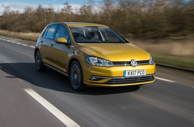 Gold VW Golf driving left to right along country road