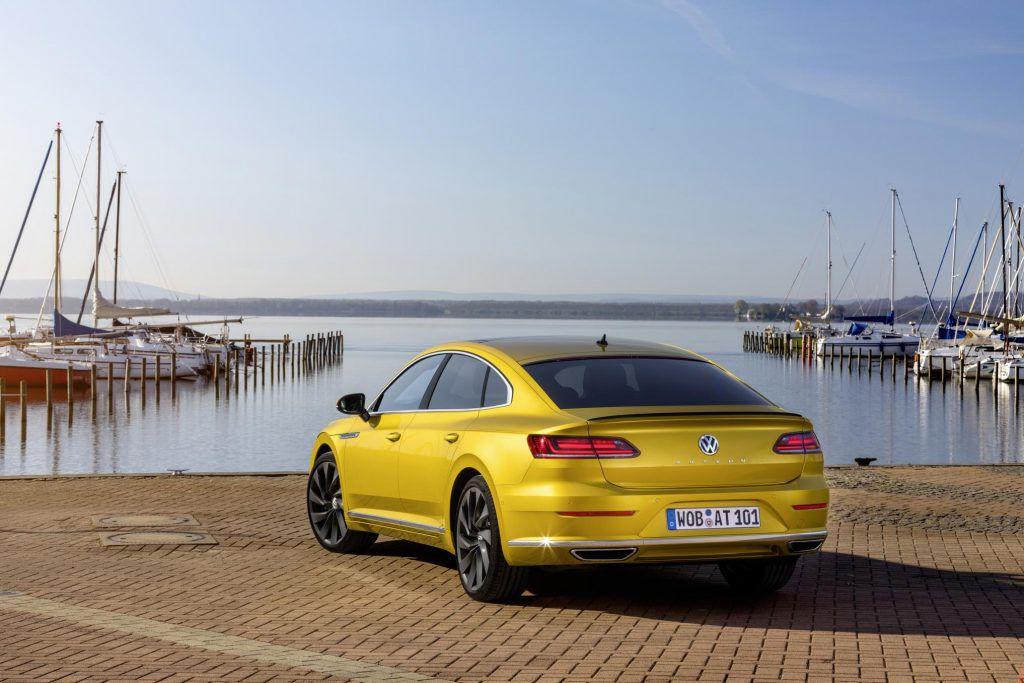 Yellow Volkswagen Arteon saloon car by the sea