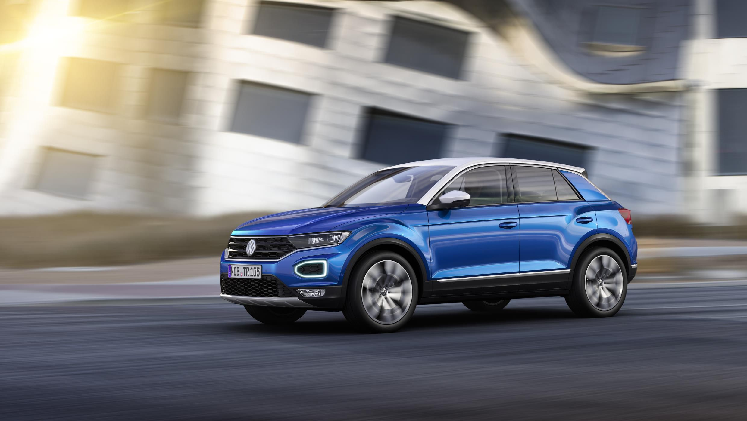Blue Volkswagen T-Roc with silver roof driving down a road with everything but the car out of focus