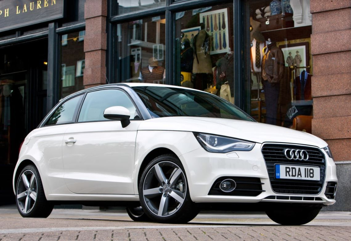 White Audi A1 parked in front of shops on city street
