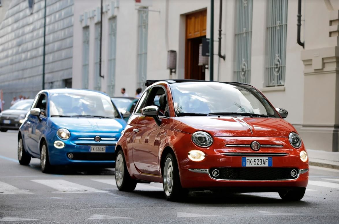 Red Fiat 500 followed by blue FIat 500 driving down a city road