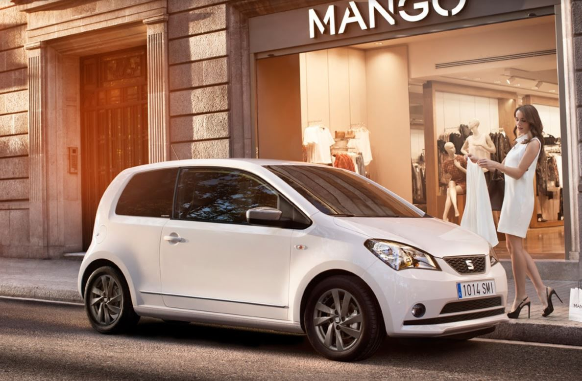 White SEAT Mii parked outside shops on city street