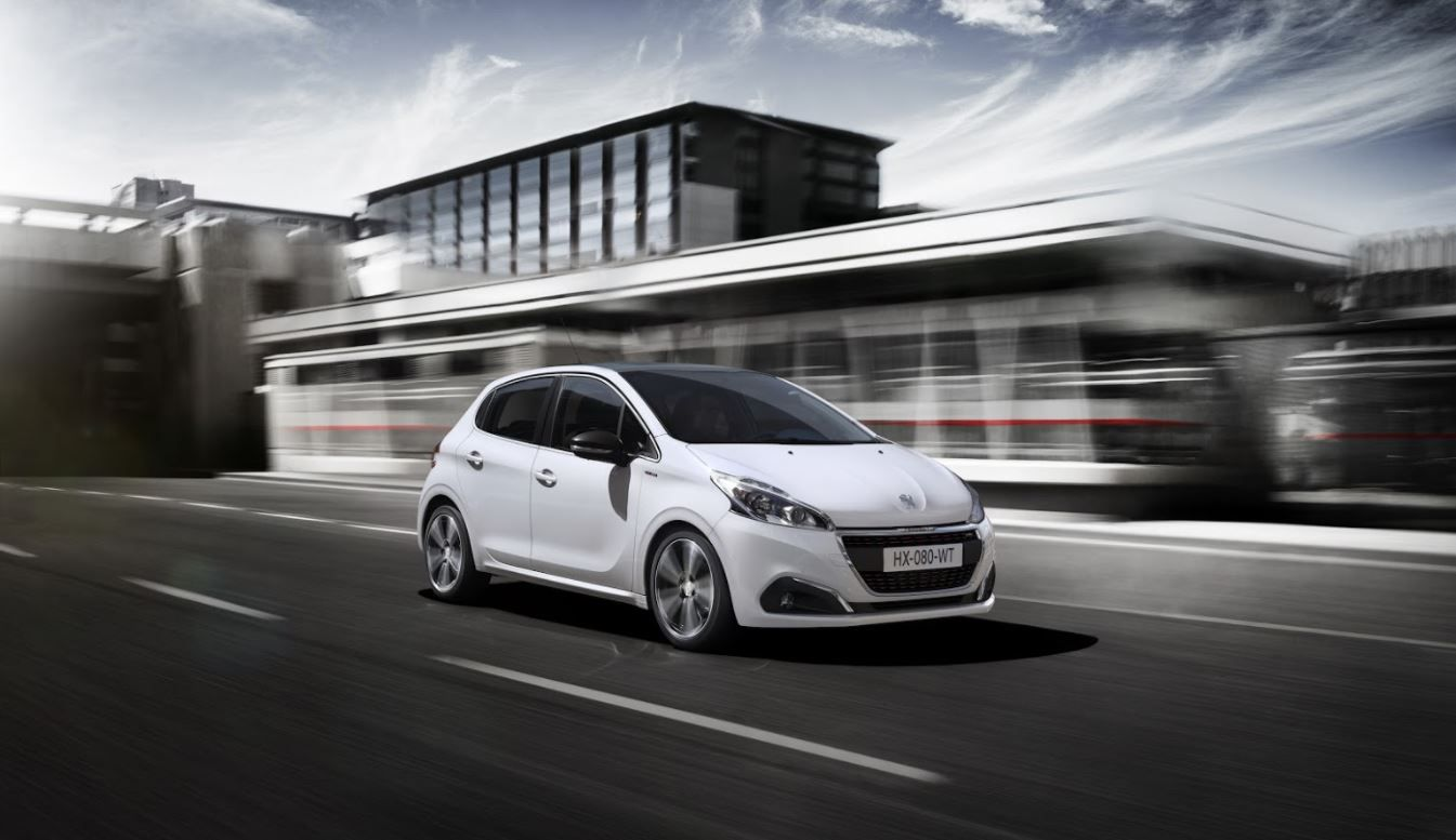White Peugeot 208 driving at speed past office buildings