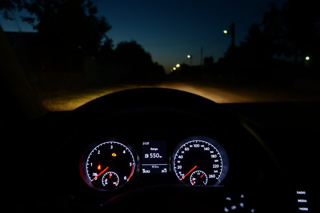 The rev counter, drivers display and speedometer lit up in a car whilst driving on the road at night