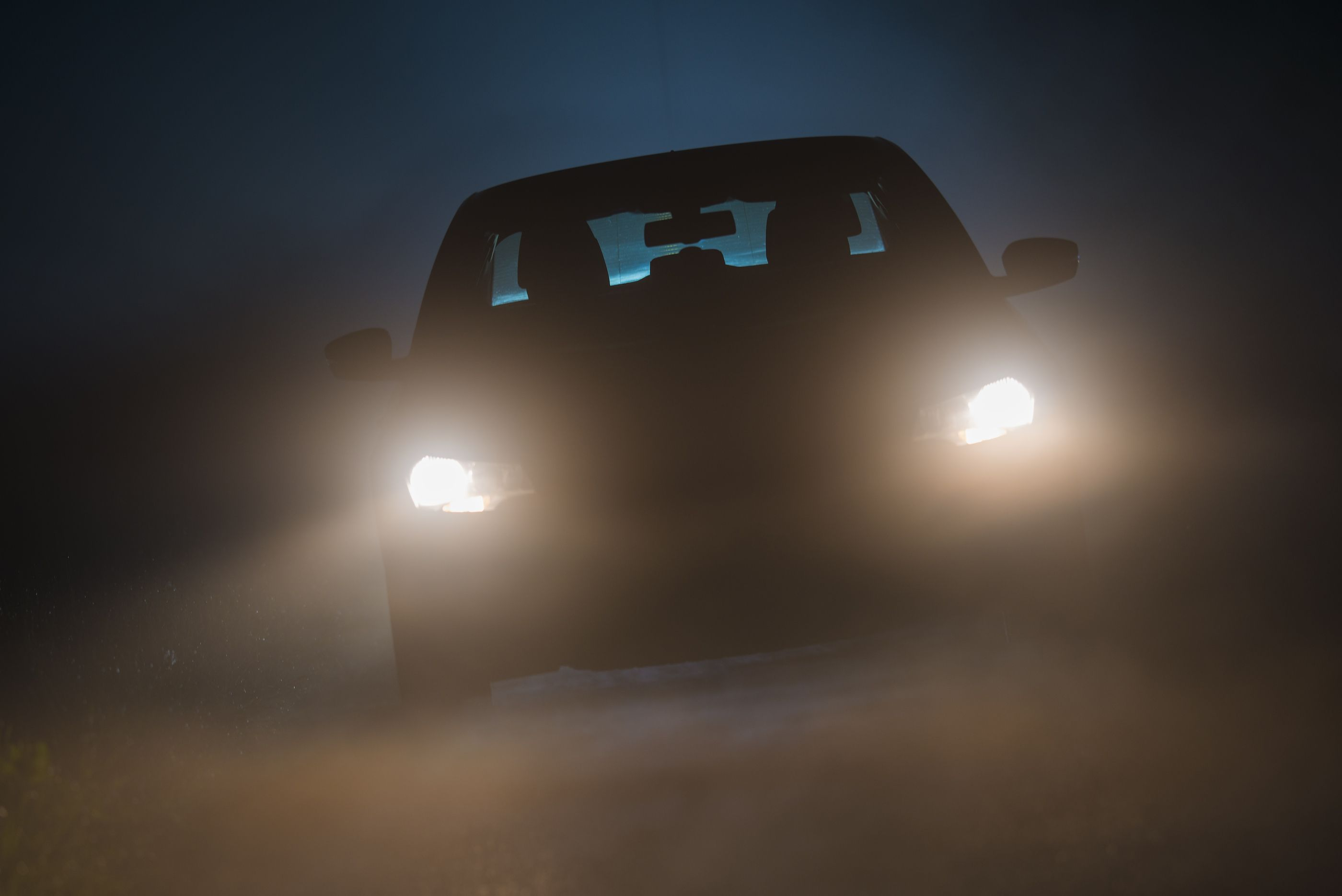 Car driving down a misty rural road with its headlights on