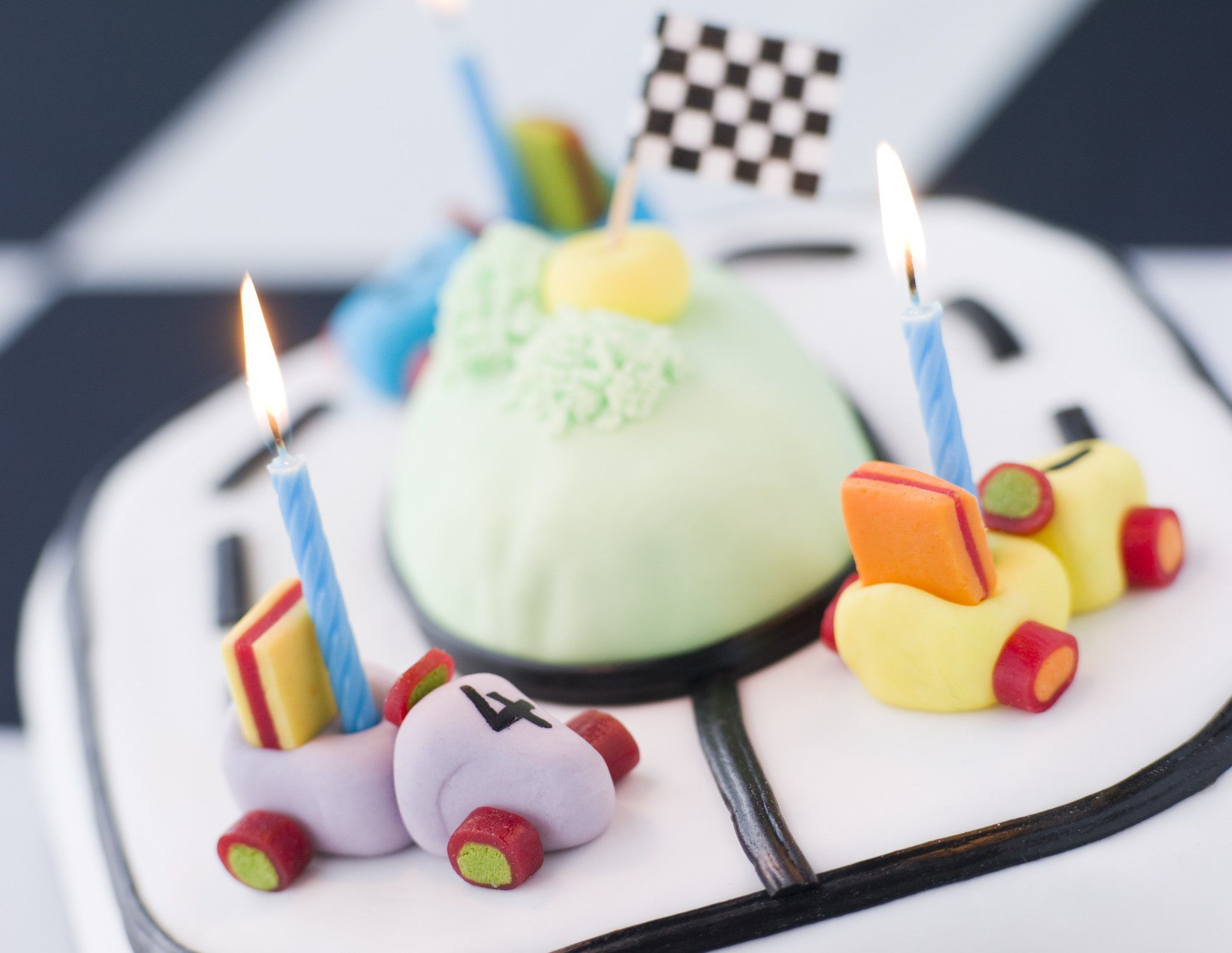 Cars made from icing and sweets on top of a cake race track