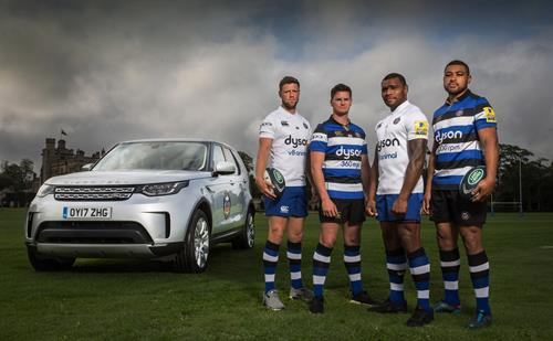 Four Rugby players stood infront and to the side of a Land Rover Discovery on a rugby pitch