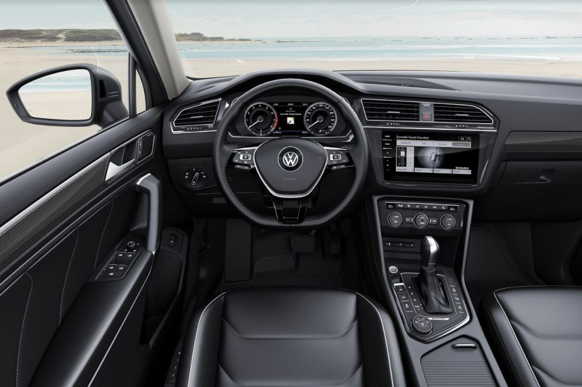 Interior of a Volkswagen showing the steering wheel, centre console, touchscreen, foot padals and leather front seats