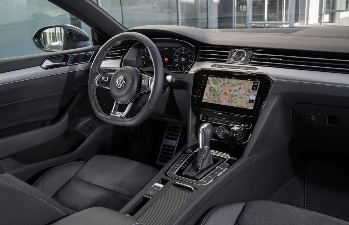 Front interior of VW car showing steering wheel and sat nav system
