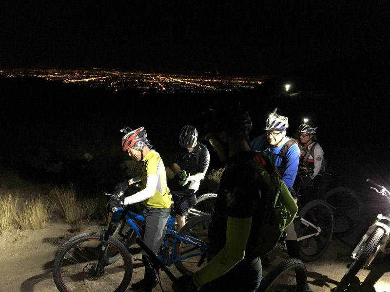 Cyclist on a mountain in the dark with helmet torches on stopped