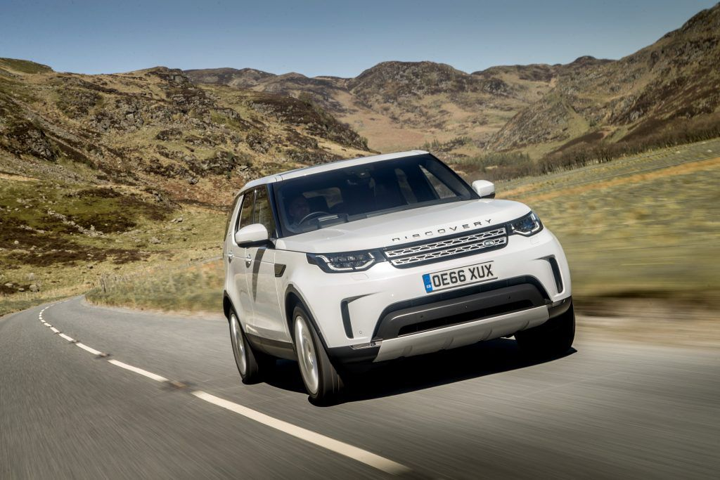 White Range Rover Discovery driving on a road through hills