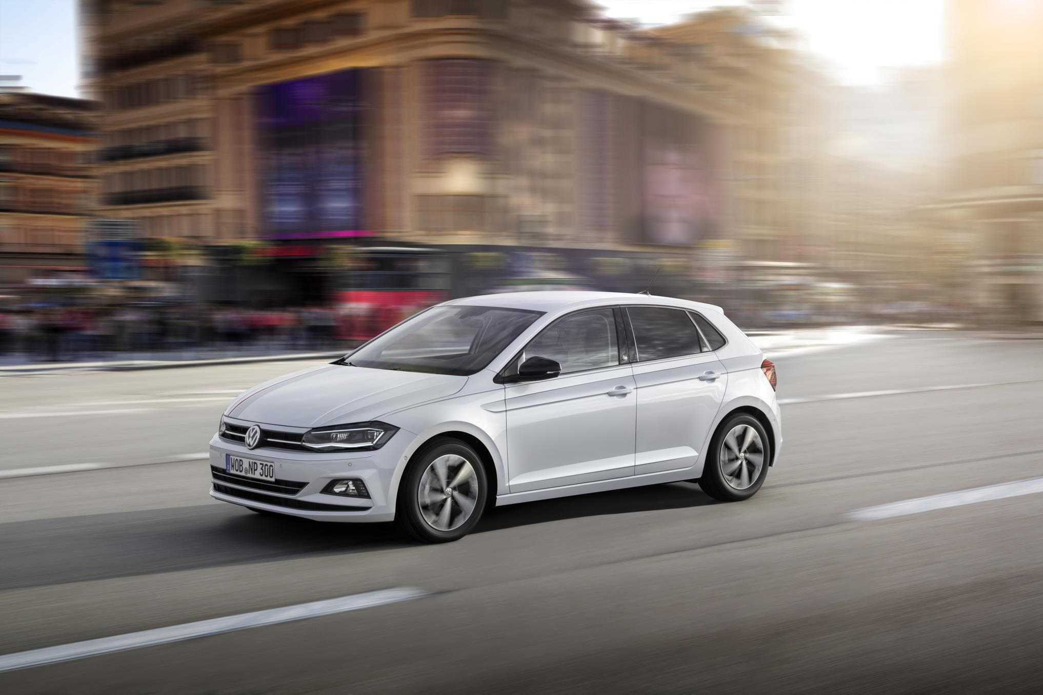 White Volkswagen Polo Beats driving down a street with a building in the background blurred as the car is driving past