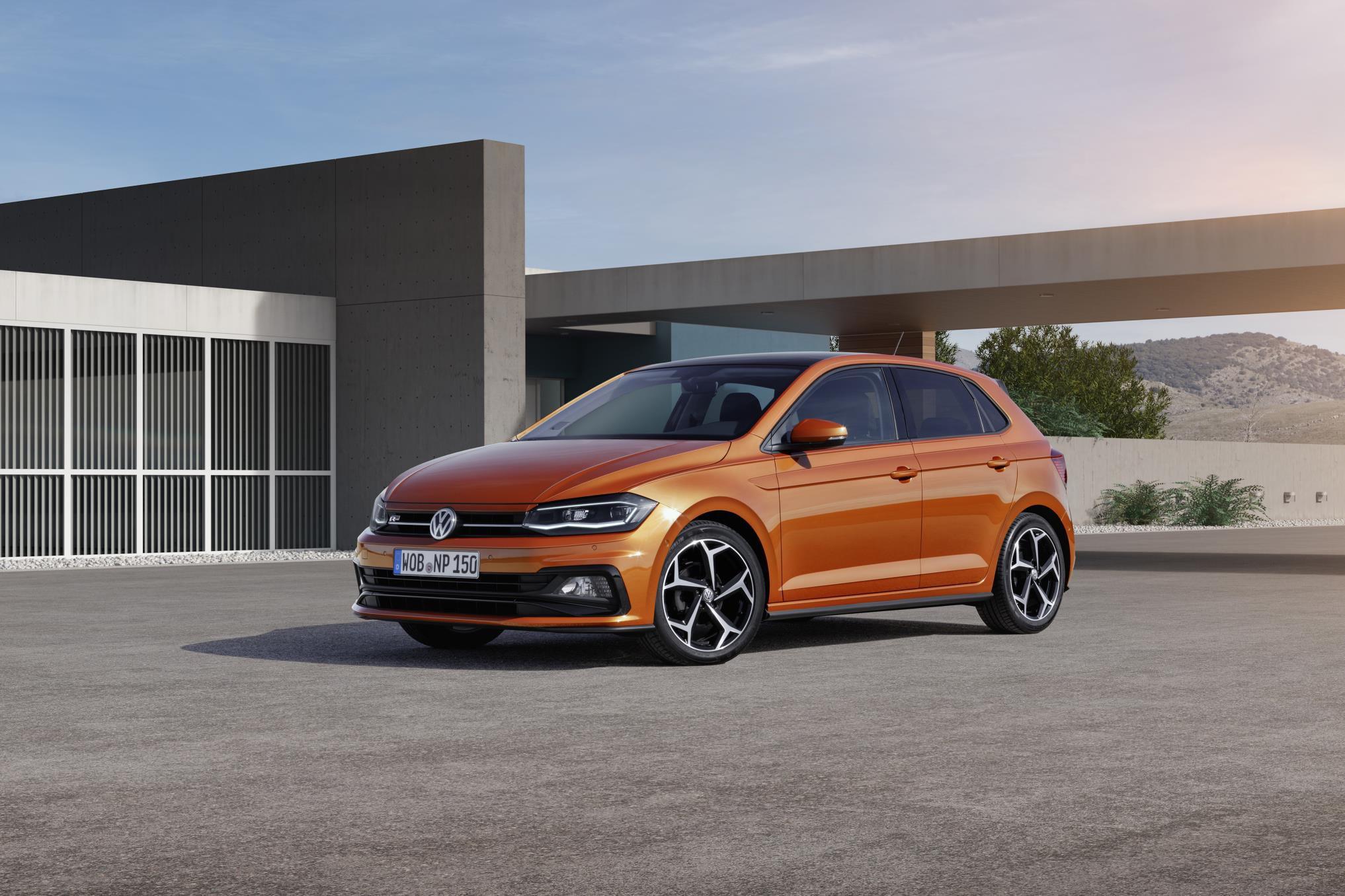 Orange new VW Polo R-Line parked by a concrete building