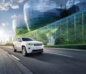 White SUV driving on main road through a built up city