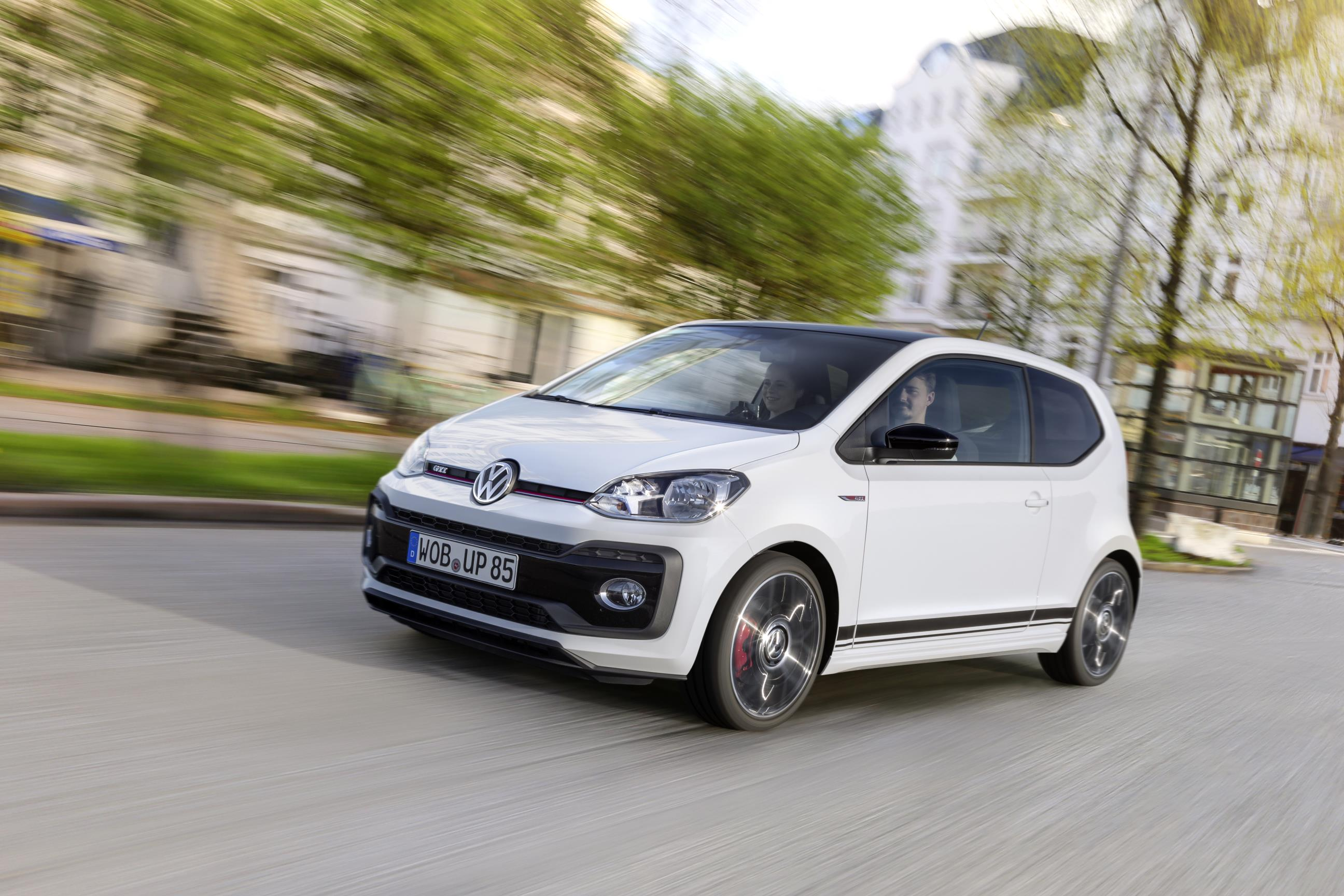 White front and side of new Volkswagen up GTI driving along the road