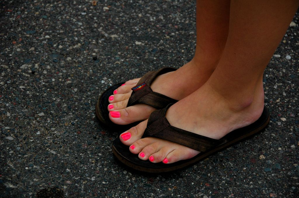 Two feet with bright pink nail polish in a pair of brown flip flop sandals