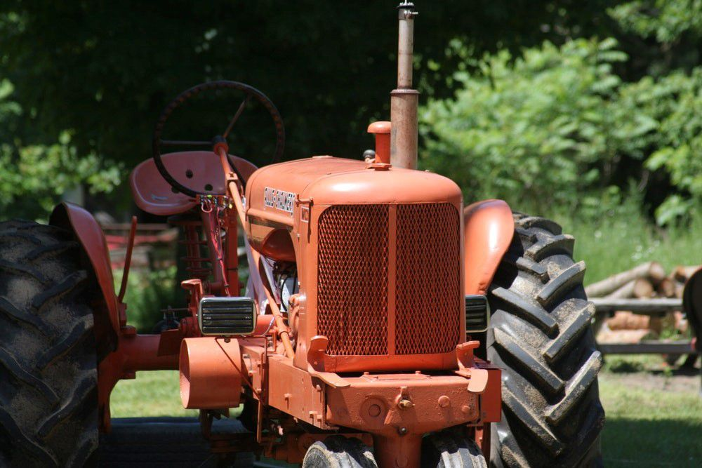 Orange tractor with big wheels in the sunshine
