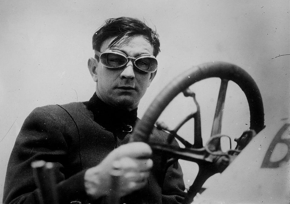 Old blackand white photograph of a man in goggles holding a steering wheel