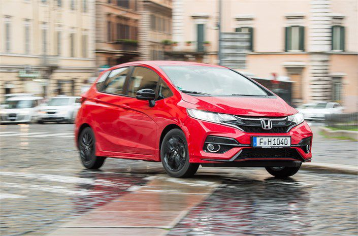 Red Honda Jazz two-thirds view in cobbled European square