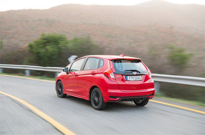 New red Honda Jazz at speed on the road going very fast