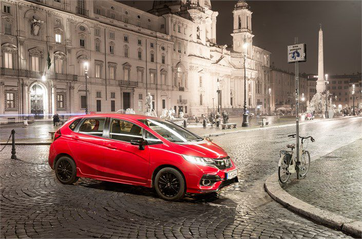 New red Honda Jazz at night in a cobbled square in Europe